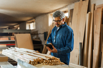 Carpenter using tablet in his workshop