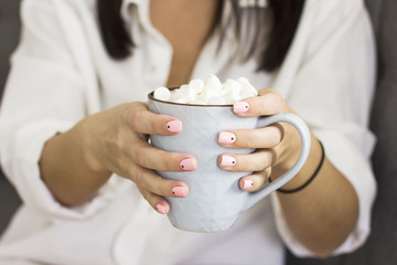 Blue mug with cocoa, coffee and marshmallows in the hands of a young brunette woman in white shirt