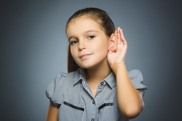 girl listens. child hearing something, hand to ear gesture on grey background.