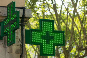 Photo sur Plexiglas Pharmacie Closeup of a green pharmacy sign outside a pharmacy store in France.
