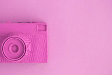 Flat lay of rose colored retro camera surrealism abstract concept