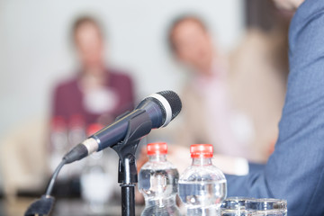 Microphone in focus against blurred people at round table event