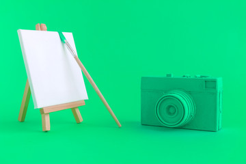 Green camera with blank art canvas and brush background.