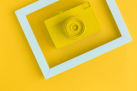 Flat lay of yellow vintage camera and photo frame background