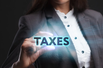 The concept of business, technology, the Internet and the network. A young entrepreneur working on a virtual screen of the future and sees the inscription: Taxes