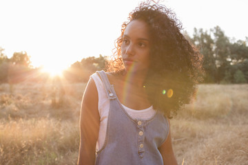 portrait outdoors of a beautiful happy young afro american woman smiling at sunset. Yellow background. Lifestyle in nature. Casual jean dress clothing