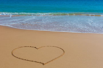 Picture of the heart on wet beach sand with the turquoise sea on background