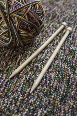 Knitting needles and yarn on wooden background/natural wool knitting background