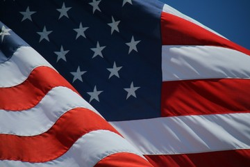 Close Up on American Flag Stars and Stripes Waving against Blue Sky in Afternoon Sun