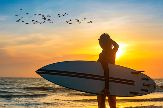 Silhouette of woman holding surfboard standing disappoint in the edge of sea wave, looking forward to the sea for sufficeint wave to surf at sunset and flock of bird in background