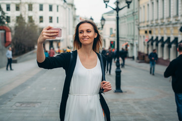 Beautiful girl makes picture in european city. Selfie is in Moscow. Girl makes selfie on the street.