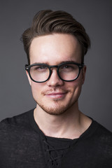 Studio portrait of a young man in big glasses
