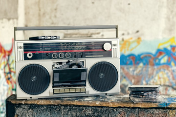Retro boombox radio with cassettes / Vintage ghetto blaster with plenty of musical cassettes on grungy background with graffiti.