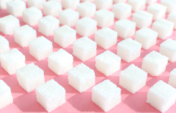 Refined sugar on pink background.Cubes of sweet and white sugar in geometricshape. Hard shadows.