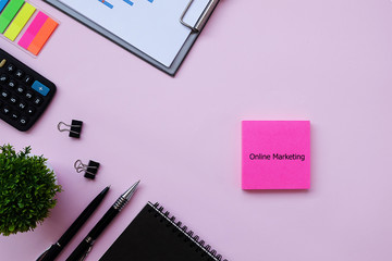 Top view pink background desktop with pink Note write text Online Marketing for business and finance concept.