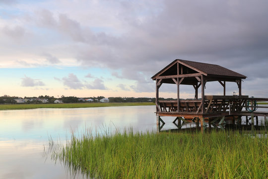 Cloudy evening landscape with beautiful colors sky reflected in a Pawleys Island bay water with private wooden dock with observation and fishing point. Myrtle Beach area, South Carolina, USA.