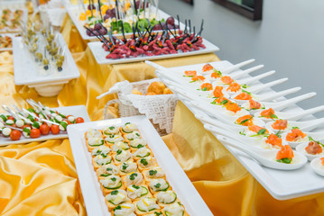 Catering table with dishes and snacks on the business event in the hotel hall. Service at business meeting, party, weddings. Selective focus, space for text.