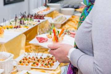 Catering buffet table with food and snacks for guests of the event. Group of people in all you can eat. Dining Food Celebration Party Concept. Service at business meeting, weddings. Selective focus.