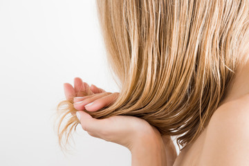 Young woman with hand touching her wet, blonde, perfect hair after shower on the white background. Care about beautiful, healthy and clean hair. Beauty salon concept. Side view.