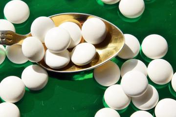Медицина. Таблетки в белой оболочке лежат на ложке из золота