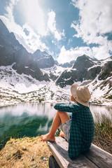 Spring summer mountain walk - boy traveler rests near beautiful mountain lake