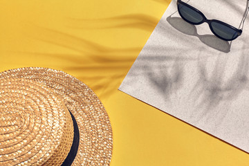 Straw beach woman's hat and sun glasses, top view yellow and white paper background with shadow from a palm leaf.