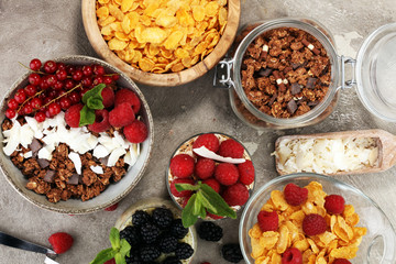 Cereal and ingredients for a healthy breakfast with chia pudding, granola, cornflakes and berries