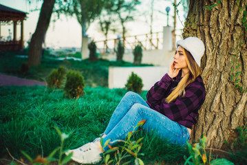 Blonde girl in the Park sitting under a tree