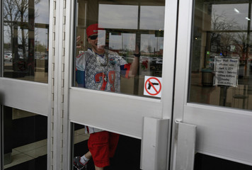 A man gestures behind a window with No Guns Allowed sign in Indianapolis