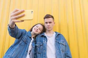 Beautiful couple makes selfie on a color background. A young couple is photographed on a smartphone. Isolated on a yellow background
