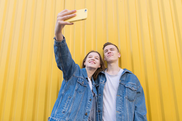 Happy, stylish pair is photographed on a smartphone on the background of a yellow wall. Man and girl make selfie on a background of yellow wall
