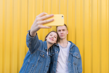 Selfies background color on the wall. Young couple doing selfie on a yellow background.