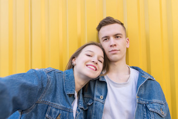 Happy young couple makes selfie on a background of yellow wall. A beautiful man and a girl are photographed. Selfies on the smartphone