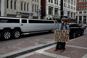Ruster, 62, a homeless man, carries a sign as he stands in the downtown of Indianapolis