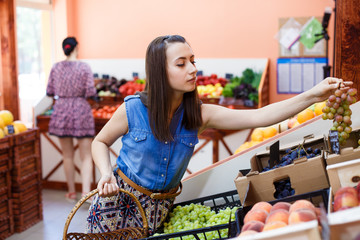 Beautiful young woman chooses grapes in a vegetable store