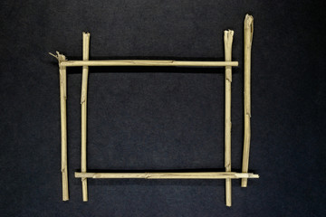 Frame from Reed Bents Straw on Black and Partly Blue Background Surface with Free Space