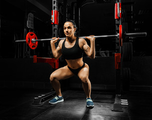 Charming girl in the gym crouches with a barbell.