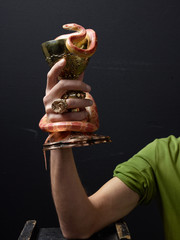 Hand holding gold chalice with snake wrapped around