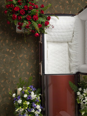 Top view of empty open coffin with floral bouquets