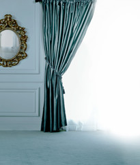 Blue curtain near sunny window