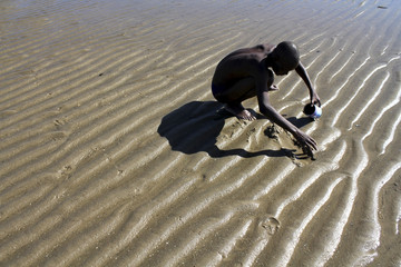 Ignacio Elias, 32, searches for clams during low tide outside of the capital Maputo