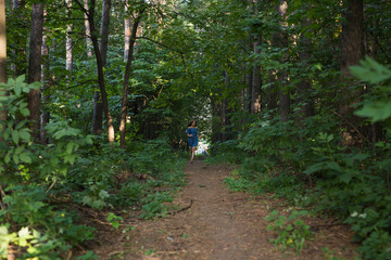 Beautiful young woman in dress runing in the summer forest