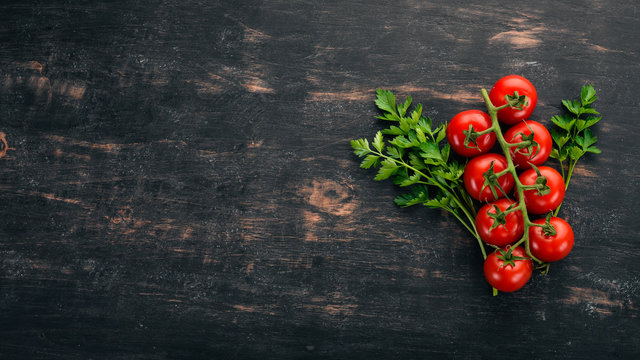 Cherry tomatoes on a twig. Top view. On a black wooden background. Copy space.