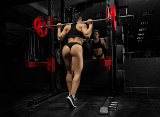 Girl with a delightful figure makes a thrust forward with a barbell.