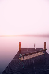 Empty footbridge with a bench on a lake Altausseer at sunrise