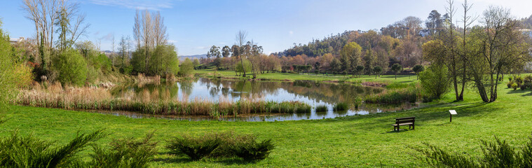 Parque da Devesa Urban Park in Vila Nova de Famalicao, Portugal. Built near the center of the city. View of the green grass lawns and lake or pond
