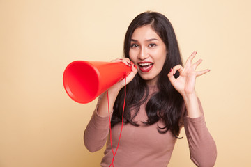 Beautiful young Asian woman show OK  announce with megaphone.