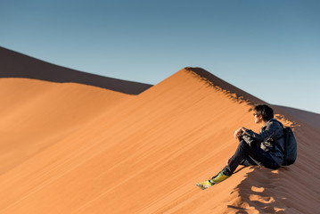 Young male traveler and photographer sitting on the top of sand dune looking at sunrise or sunset in desert of Namibia, Africa. Travel photography concept