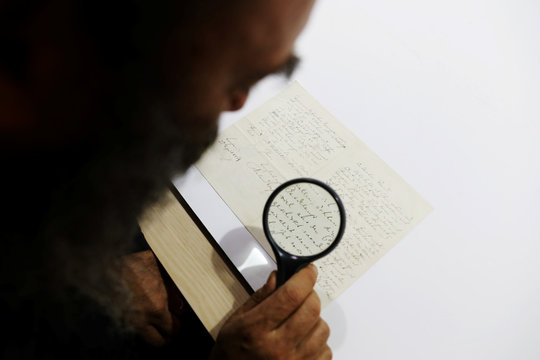 Meron Eren of Kedem Auction House uses a magnifying glass to look at a letter handwritten by composer Richard Wagner in 1869, before it is sold at an auction in Jerusalem