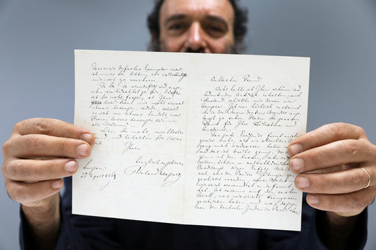 Meron Eren of Kedem Auction House holds a letter handwritten by composer Richard Wagner in 1869, before it is sold at an auction in Jerusalem